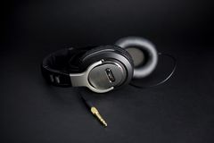 Stereo headphones. Old school leathered stereo headphones on a black backdrop Stock Photos