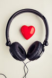 Stereo headphones with red heart symbol. Beige background royalty free stock photography