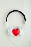Stereo headphones with red heart symbol. White background stock photography
