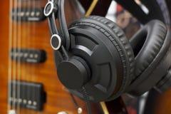 Stereohoofdtelefoons met gitaar, de opnameconcept van het huis volkslied, uitstekende stijl De muziek onderhoudt hoofdtelefoon en royalty-vrije stock foto