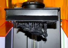 Stereolithography DPL 3d printer create small detail and liquid drips. Stereolithography DPL 3d printer create detail and liquid drips, platform slowly move with Royalty Free Stock Photos