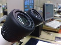 Stereomicroscope eyepieces. In foreground, pc monitor in background Royalty Free Stock Photo