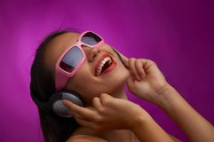 Stereotype. Glamour portrait of young brunette in pink sunglasses listening music Royalty Free Stock Photos