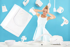 Stereotypical lady of the house - cleaning , feathers, cooks , vacuumsing around the house . Young housewife overwhelmed by tasks associated with running a home Stock Photo