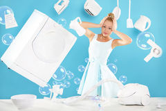 Stereotypical woman of the house - cleaning , feathers, cooks , vacuumsing around the house . Young housewife overwhelmed by tasks associated with running a Royalty Free Stock Photo