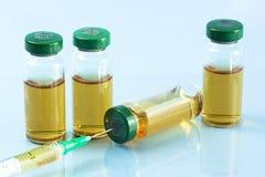 Steriele medische flesjes met medicijnoplossing, ampullen, en spuit op een lichtblauwe achtergrond Royalty-vrije Stock Fotografie
