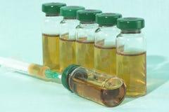 Steriele medische flesjes met medicijnoplossing, ampullen, en spuit op een lichtblauwe achtergrond Royalty-vrije Stock Foto's