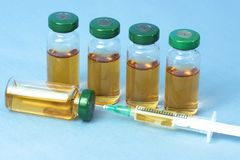 Steriele medische flesjes met medicijnoplossing, ampullen, en spuit op een lichtblauwe achtergrond Royalty-vrije Stock Foto
