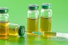 Steriele medische flesjes met medicijnoplossing, ampullen, en spuit op een lichtgroene achtergrond Royalty-vrije Stock Foto