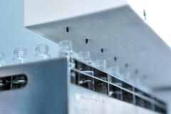Sterila kapslar för injektion Flaskor på den buteljera linjen av den farmaceutiska växten Maskin, når att ha kontrollerat som är  Royaltyfri Fotografi