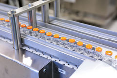 Sterile capsules for injection. Bottles on the bottling line of the pharmaceutical plant. Machine after checking sterile Stock Image