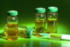 Sterile medical vials with medication solution, ampoules, and syringe  on a green background Royalty Free Stock Image