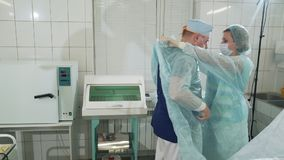Sterile operating theater. The doctor is getting ready for surgery. The nurse helps him put on a special gown and gloves. Department of Surgery in the hospital stock video footage