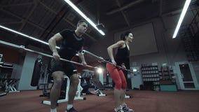 Sterk atletisch paar die in een gymnastiek uitwerken stock videobeelden