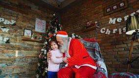 Sterk omhels tussen gelukkig vrouwelijk die kind van meisje en Santa Claus in ruimte voor Kerstmis wordt verfraaid stock video