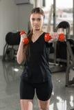 Sterk vrouwengewichtheffen bij de gymnastiek die gelukkig kijken Stock Foto's