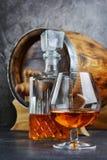 Sterke alcoholisch drinkt cognac in snifferglas met kristalkaraf en uitstekend houten vat in kelder stock fotografie
