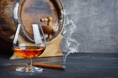 Sterke alcoholisch drinkt cognac in snifferglas met rokende sigaar en uitstekend houten vat in kelder royalty-vrije stock foto's
