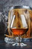 Sterke alcoholisch drinkt cognac in snifferglas met rokende sigaar in kristalasbakje en uitstekend houten vat royalty-vrije stock afbeelding