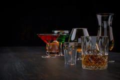 Sterke alcoholische dranken, glazen en glazen, in aanwezigheid van whisky, wodka, rum, tequila, brandewijn, cognac op een donkere royalty-vrije stock afbeeldingen