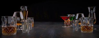 Sterke alcoholische dranken, glazen en glazen, in aanwezigheid van whisky, wodka, rum, tequila, brandewijn, cognac op een donkere stock foto's