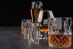 Sterke alcoholische dranken, glazen en glazen, in aanwezigheid van whisky, wodka, rum, tequila, brandewijn, cognac op een donkere stock afbeelding