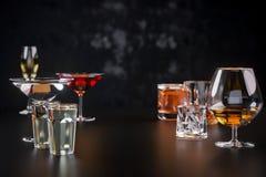 Sterke alcoholische dranken, glazen en glazen, in aanwezigheid van whisky, wodka, rum, tequila, brandewijn, cognac op een donkere royalty-vrije stock foto's