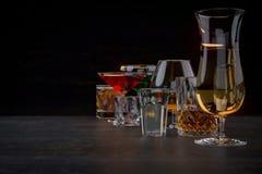 Sterke alcoholische dranken, glazen en glazen, in aanwezigheid van whisky, wodka, rum, tequila, brandewijn, cognac op een donkere royalty-vrije stock afbeelding