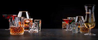 Sterke alcoholische dranken, glazen en glazen, in aanwezigheid van whisky, wodka, rum, tequila, brandewijn, cognac op een donkere stock foto