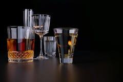 Sterke alcoholische dranken, glazen en glazen, in aanwezigheid van whisky, wodka, rum, tequila, brandewijn, cognac op een donkere stock afbeeldingen