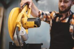 Sterke arbeider die hoekige malende machine in workshop met behulp van Het onderhouden van machines stock foto