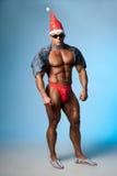Sterke atletische mens in een santahoed en donkere glazen Stock Foto