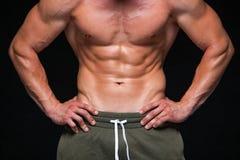 Sterke Atletische Mens - Geschiktheidsmodel die zijn perfect die lichaam tonen op zwarte achtergrond met copyspace wordt ge?solee stock foto