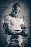 Sterke bodybuilder atletische mens die omhoog spierentraining pompen bodyb stock foto's