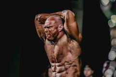 Sterke de spanningspers van de atletenbodybuilder, handen achter uw hoofd Stock Foto