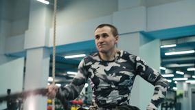 Sterke dichte omhooggaand van de spiermens trekt slagkabel in de gymnastiek in langzame motie stock footage