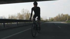 Sterke en geschikte fietser met baard die zwarte uitrusting, helm en zonnebril dragen die fiets berijden uit het zadel De voorzij stock videobeelden