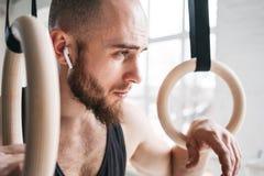 Sterke gebaarde atleet met de draadloze crosstraining ringen van de hoofdtelefoonholding bij crossfitzaal stock fotografie