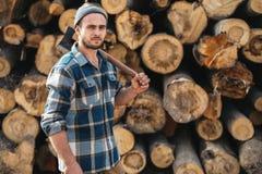 Sterke gebaarde houthakker die de greepbijl van het plaidoverhemd ter beschikking op achtergrond van zaagmolen dragen royalty-vrije stock afbeeldingen