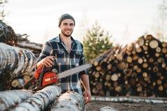 Sterke gebaarde houthakker die de greepkettingzaag van het plaidoverhemd ter beschikking op achtergrond van zaagmolen dragen royalty-vrije stock foto's