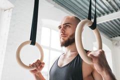Sterke gebaarde mens die gymnastiek- ringen houden bij gymnastiek stock foto
