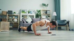 Sterke geschikte jonge mens die opdrukoefeningen op vloer doen en het smartphonescherm bekijken stock video