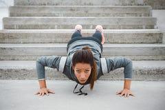 Sterke geschiktheids stedelijke vrouw die duw UPS doen royalty-vrije stock fotografie