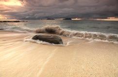 Sterke golven en grote rots op het strand Royalty-vrije Stock Afbeelding