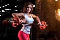 Sterke jonge vrouw met mooi atletisch lichaam die oefeningen met barbell doen stock afbeelding