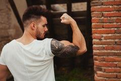 Sterke kerel met een buiten tatoegering op zijn wapen Stock Afbeeldingen