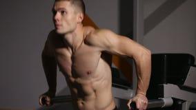 Sterke krachtige mannelijke oefeningen voor pectoral spieren en triceps met onderdompelingen Close-up, hulp van het lichaam stock video