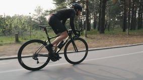 Sterke magere geschikte fietser die een fiets in het park berijden Hoge snelheid het cirkelen helling uit het zadel De partij vol stock footage