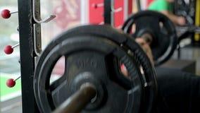 Sterke mannelijke bodybuilder die de oefening van de bankpers met zware barbell in gymnastiek doen stock footage