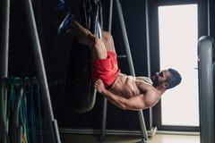Sterke mens in de gymnastiek die abs oefening doen royalty-vrije stock afbeelding